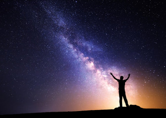 Milky Way. Night sky with stars and silhouette of a man with raised-up arms
