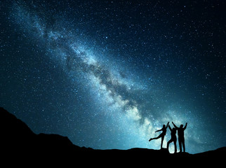 Landscape with colorful green Milky Way. Night starry sky with silhouette of a sporty happy family with raised-up arms on the mountain. Beautiful Universe. Space background