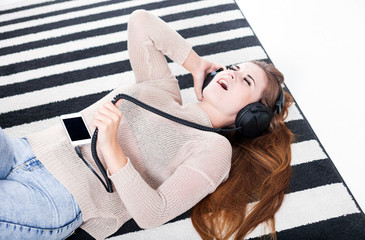 Woman with headphones singing and listening to music at home