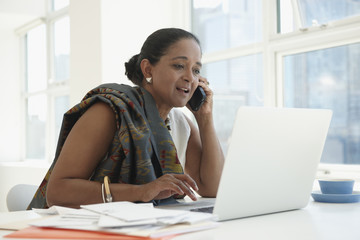 Indian businesswoman using cell phone at desk