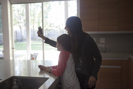 Mixed race mother and daughter taking selfie in kitchen