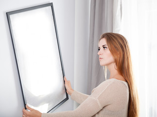 Woman hanging picture frame at her new home