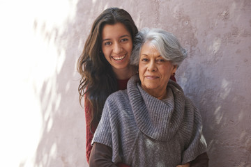 Older Hispanic woman and granddaughter smiling