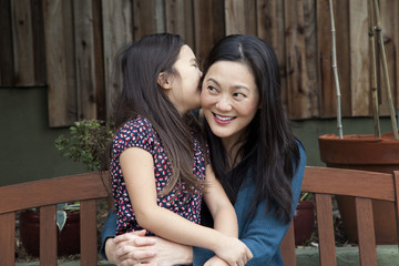 Mother and daughter whispering secrets in backyard