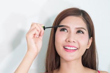 Makeup woman putting mascara eye make up on eyes. Asian fresh fa