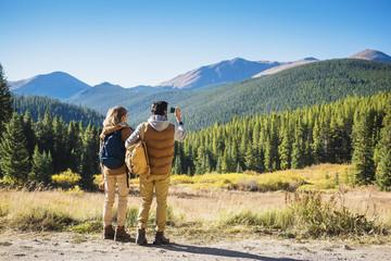 Hispanic couple photographing mountains, Breckenridge, Colorado, United States,