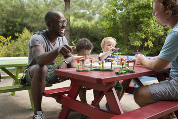 Fathers and toddler sons playing at picnic table