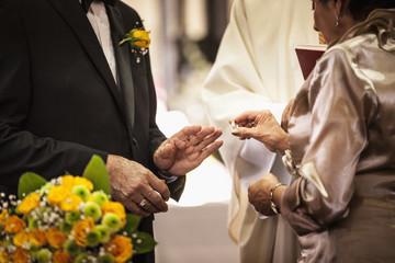 Senior couple exchanging rings at wedding