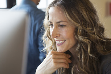 Close up of smiling businesswoman working at computer