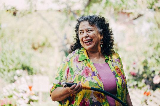 Hispanic woman watering plants in garden