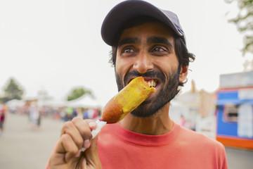 Asian man eating corn dog outdoors