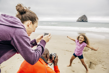 Parents taking picture of daughter on beach