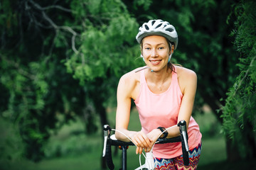 Smiling Caucasian woman leaning on bicycle handlebar