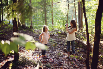 Caucasian girl photographing sister in forest