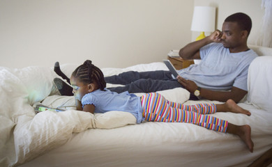 African American father and daughter relaxing on bed