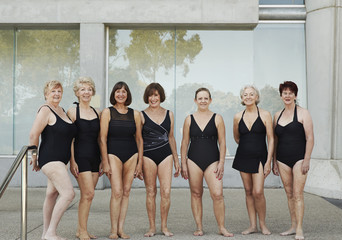 Older Caucasian women wearing black bathing suits at pool
