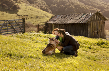 Couple petting dog in rural landscape