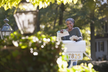 Mixed race woman reading mail at mailbox