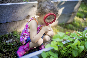 Girl examining garden plants with magnifying glass