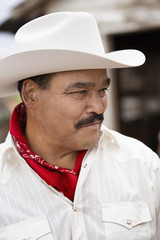 Hispanic man wearing cowboy hat outdoors