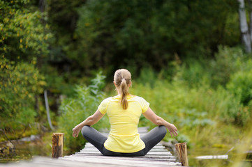 Woman in Lotus position near the river.
