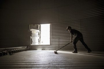 Young boy sweeping empty silo