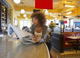 African American woman reading newspaper in cafe