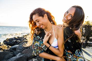 Women laughing on rocky beach