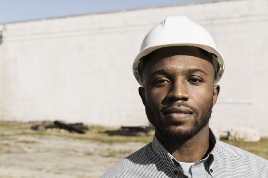 Close up portrait of Black man wearing hard-hat at construction site