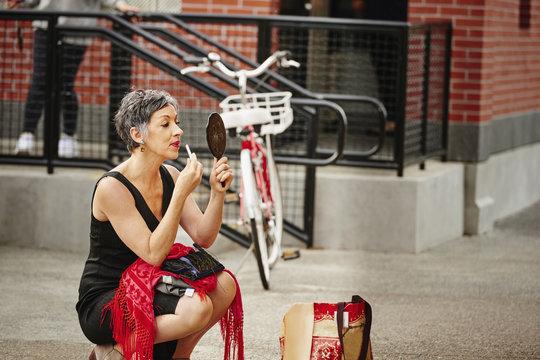 Older Caucasian woman applying makeup in mirror on sidewalk