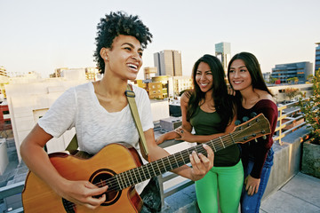 Woman playing guitar for friends on urban rooftop