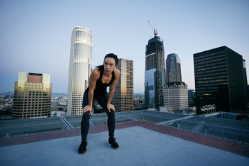 Caucasian woman resting on urban rooftop