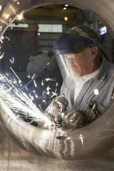 Caucasian welder working on pipe