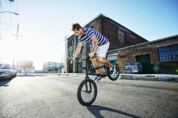 Caucasian man riding BMX bike on street
