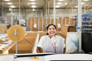 Female worker in factory laughing