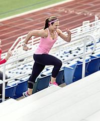 Caucasian athlete running up bleachers