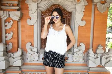 Woman wearing sunglasses near decorative window