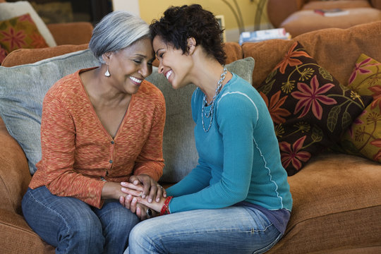 African American mother talking with daughter in living room