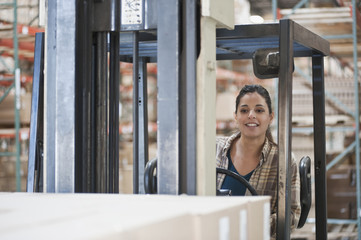 Mixed race woman operating forklift in warehouse