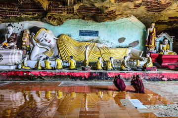Monks praying in front of Reclining Buddha statue