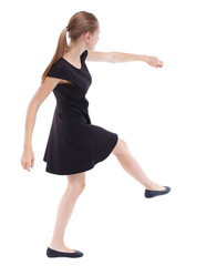 skinny woman funny fights waving his arms and legs. Isolated over white background. Blonde in a short black dress kicking ball