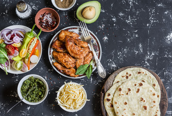 Spicy grilled chicken, tortilla, avocado, cheese, vegetables on a dark background, top view