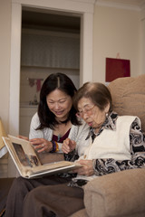 Asian mother and daughter looking at photo album