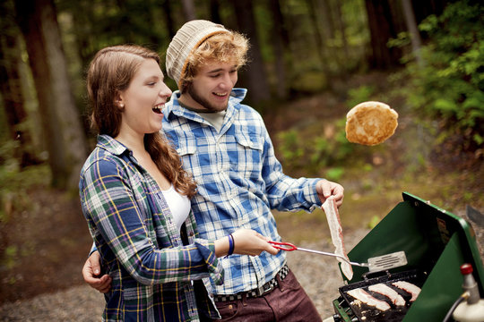 Couple cooking at camp stove in forest