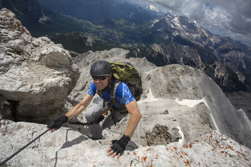 Caucasian climber scaling remote mountain slope