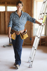 Caucasian construction worker leaning on ladder in unfinished room