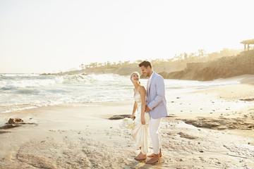 Newlywed couple hugging on beach