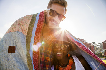 Couple wrapped in blanket smiling outdoors