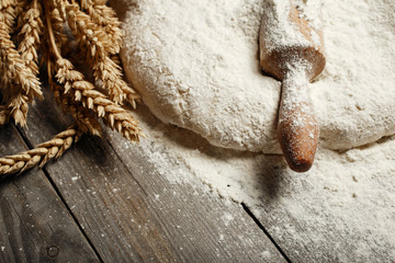 Wall Mural - Dough with wooden rolling pin and wheat