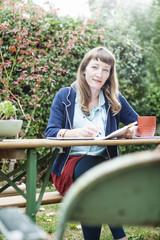 Mixed race businesswoman writing notes in backyard